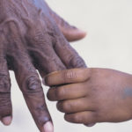 What is in your hand image showing a man holding the hands of a child