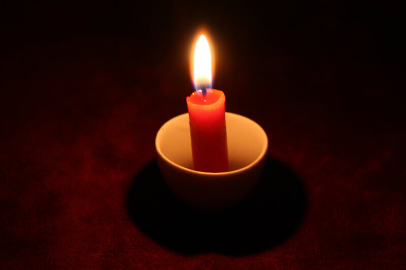 Thou wilt light my candle showing a candle in the dark