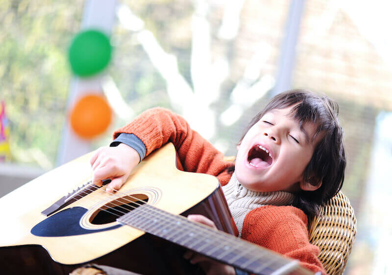 sing a new song unto the Lord showing  child with a guitar